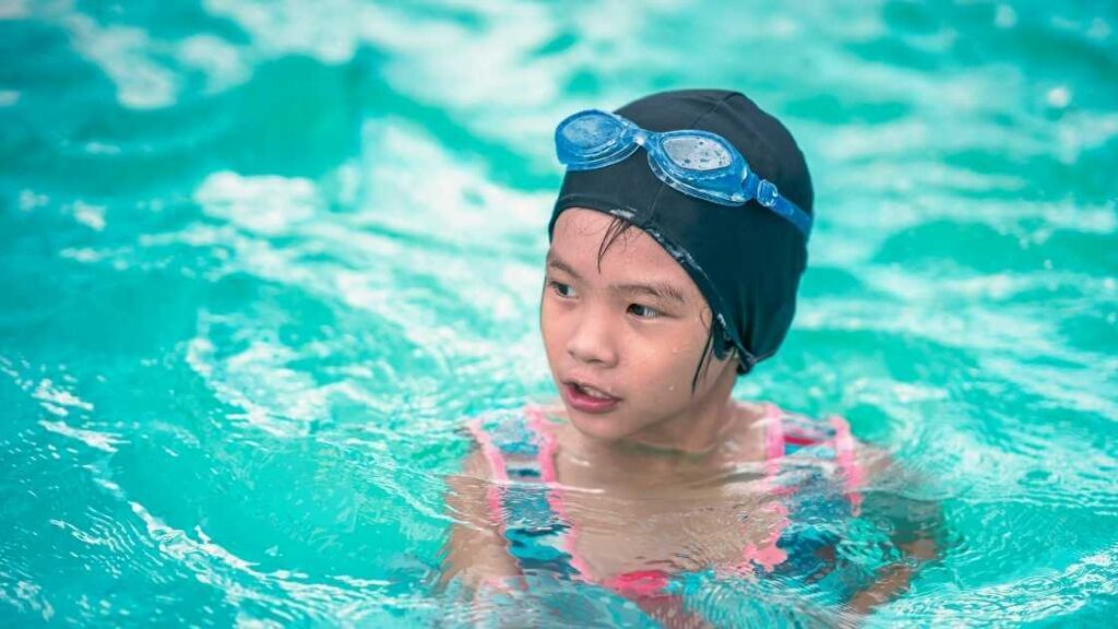 Girl with goggle swimming in pool, she has year-long swimming lessons